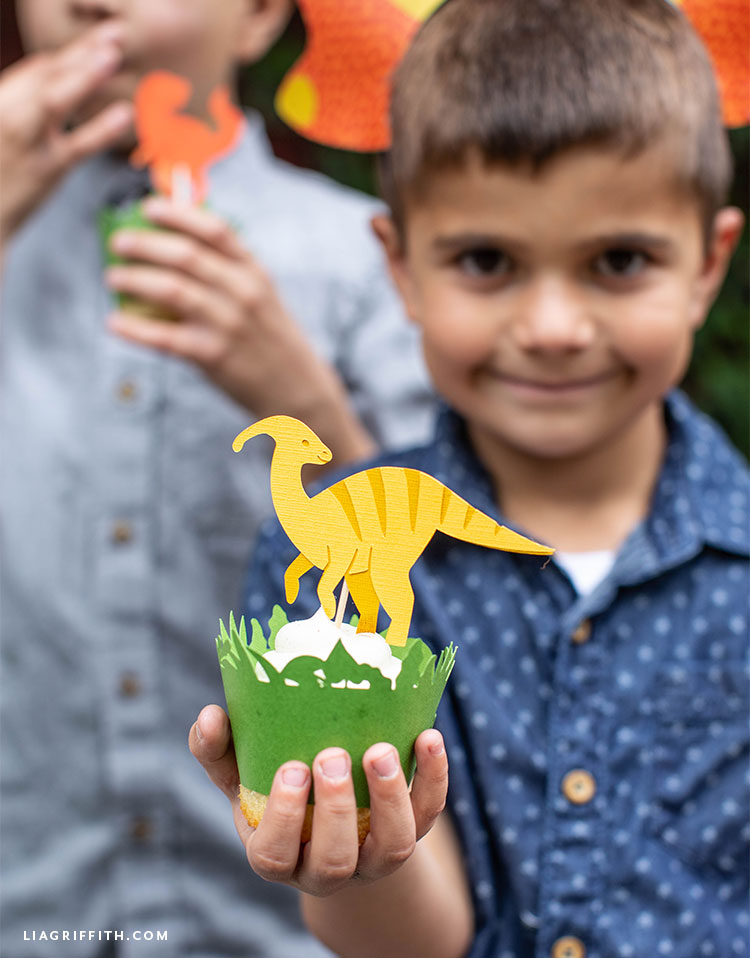 Little boy holding cupcake with dinosaur topper