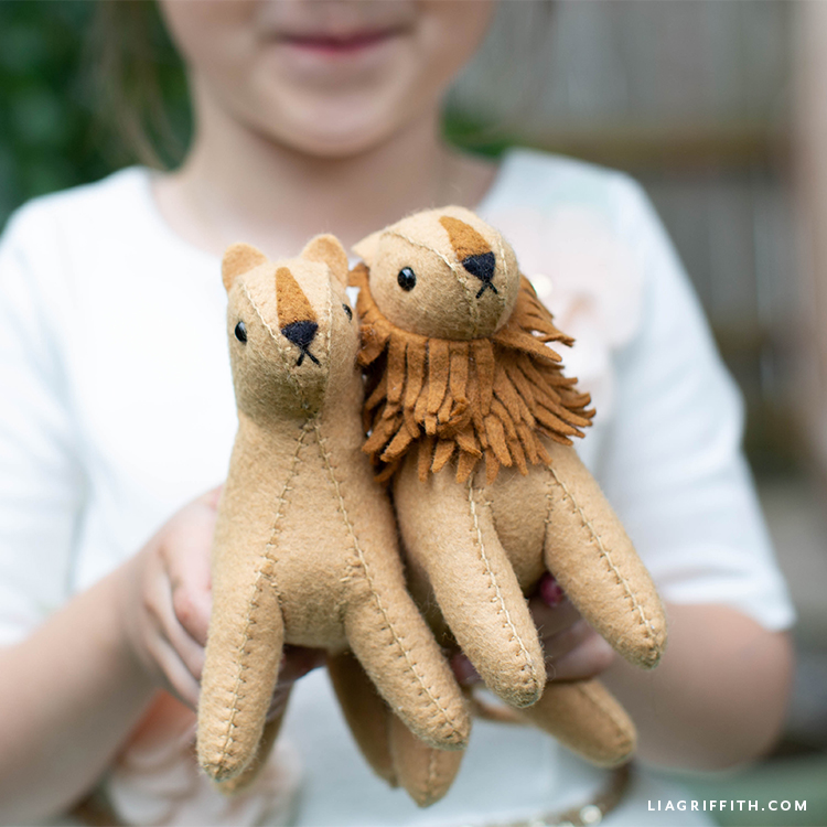 Kid holding felt lion and felt lioness