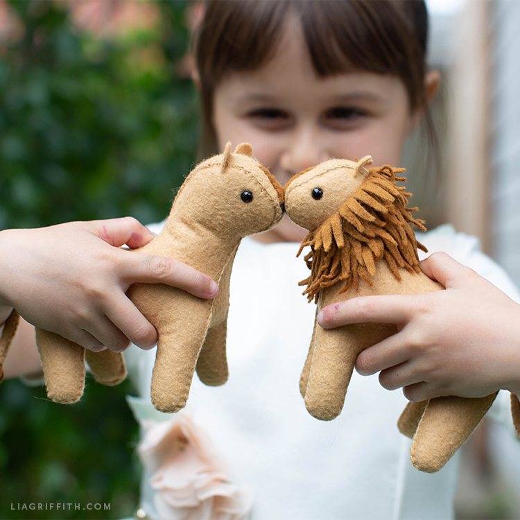 Little girl holding felt lion and felt lioness