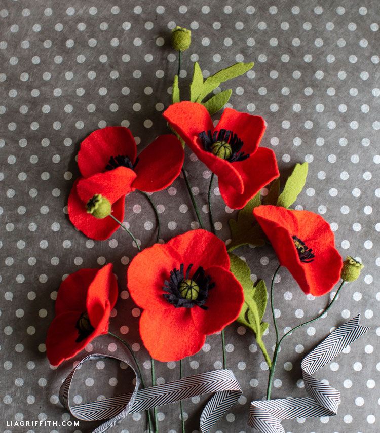 felt red poppies with black and white ribbon on grey and white polka-dot background