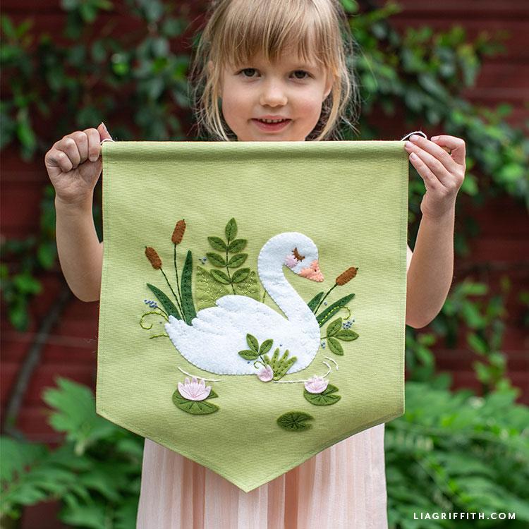 Girl holding felt swan banner