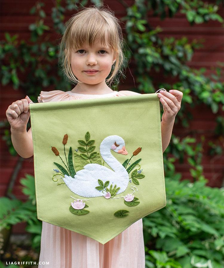 girl holding swan banner