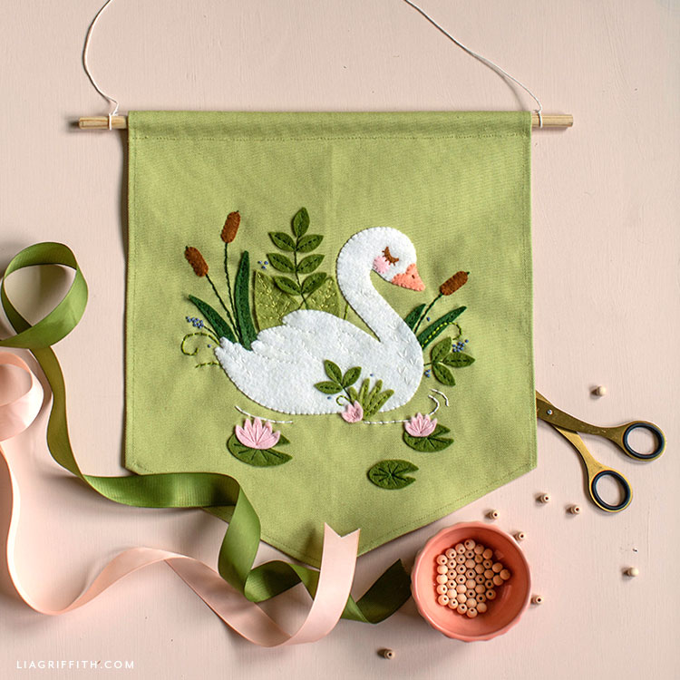 felt applique swan banner next to green and pink ribbon, wooden beads, and scissors