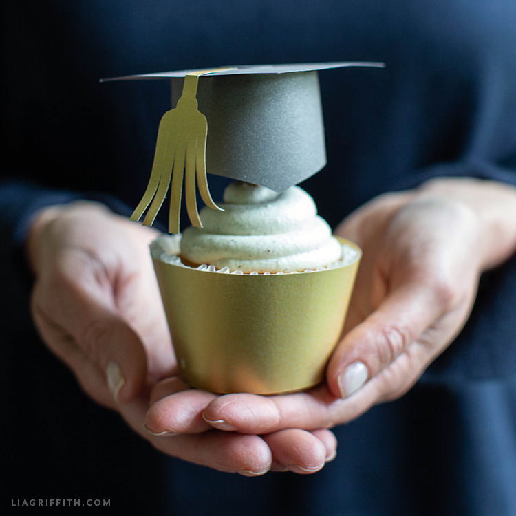 person holding graduation cupcake with graduation cap cupcake topper