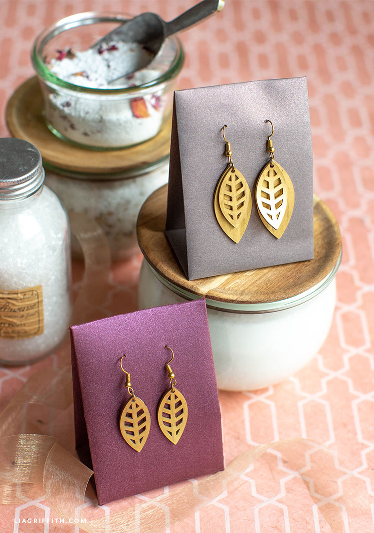 DIY gold leaf earrings hanging in earring holders on top of DIY bath and beauty products