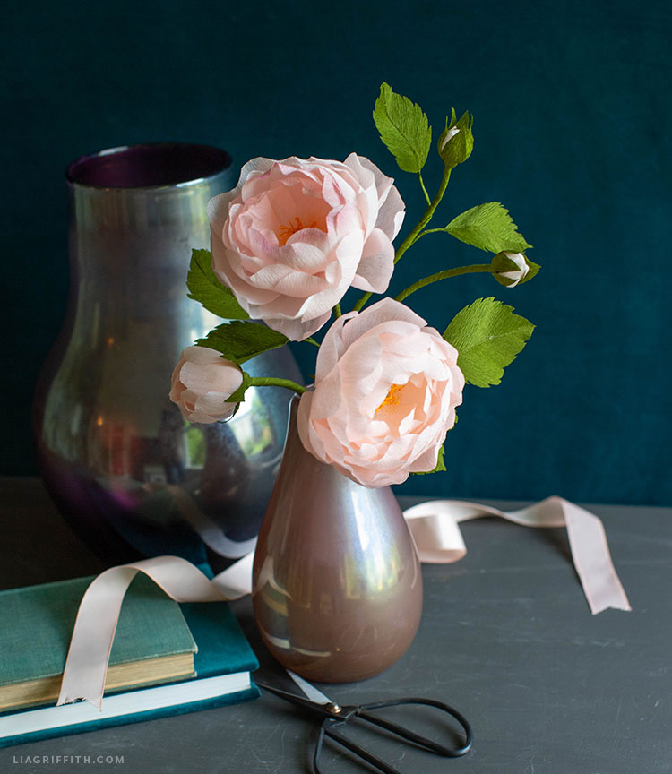 crepe paper Scarborough Fair roses in vase next to pink ribbon, empty vase, and books