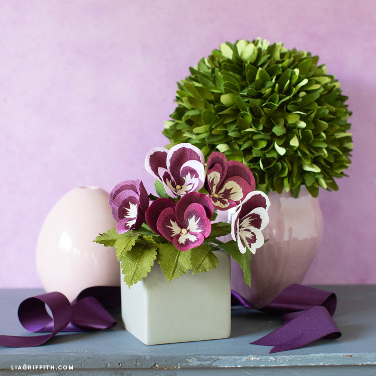 crepe paper pansies in small grey container next to crepe paper topiary, purple ribbon, and empty pink vase
