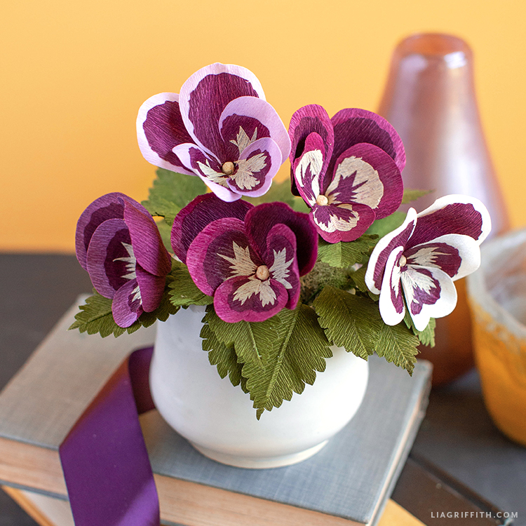 crepe paper pansies in white pot on top of books