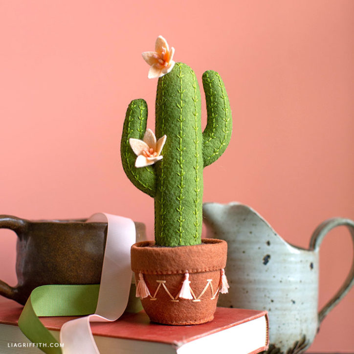 stuffed felt saguaro cactus in decorative pot on top of book next to pitcher