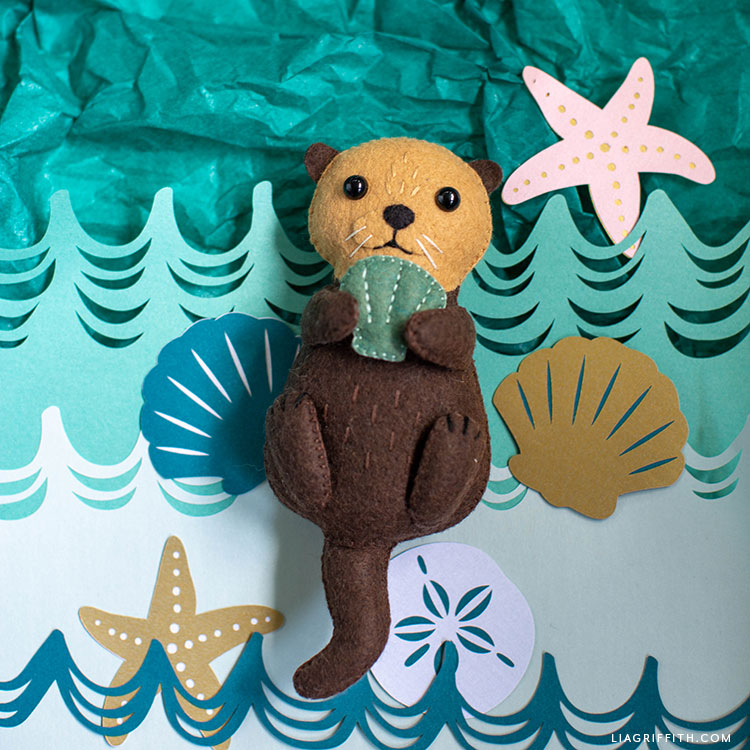 felt sea otter stuffie with felt seashell and papercut shells and starfish