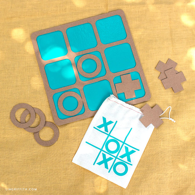 Chipboard and vinyl tic-tac-toe board with XO game pieces and bag