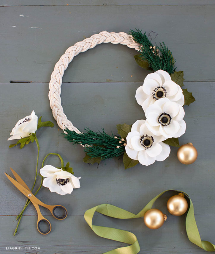 braided rope wreath with crepe paper anemones and holiday greenery