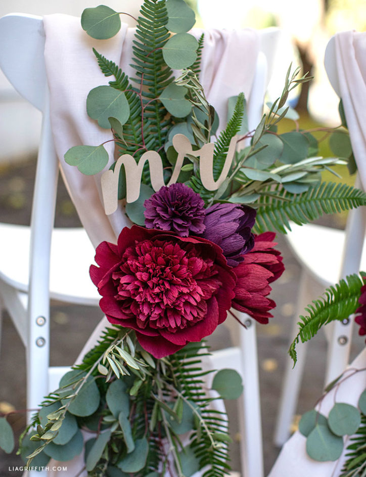 wedding chair decorations featuring crepe paper flowers, fresh greenery, and mr. sign