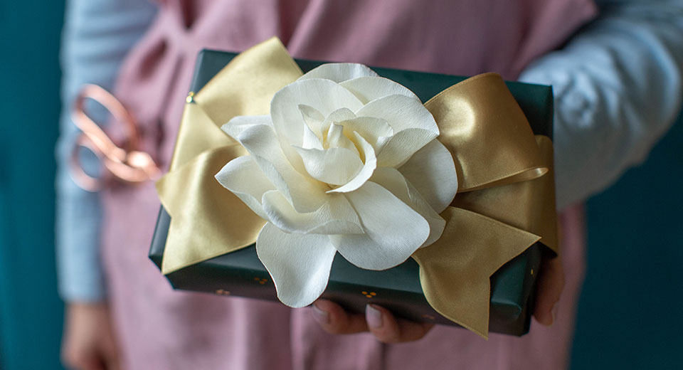 A crafter handing the viewer a gift with a beauiful flower bow.