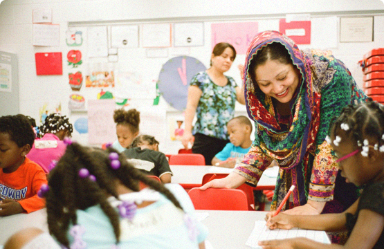 woman helping children in the classroom
