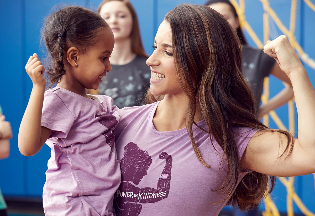 Aly Raisman holding a young girl