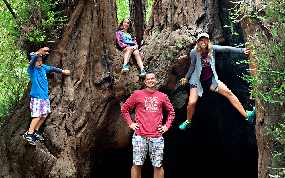 Casey's family sitting in a giant red wood tree