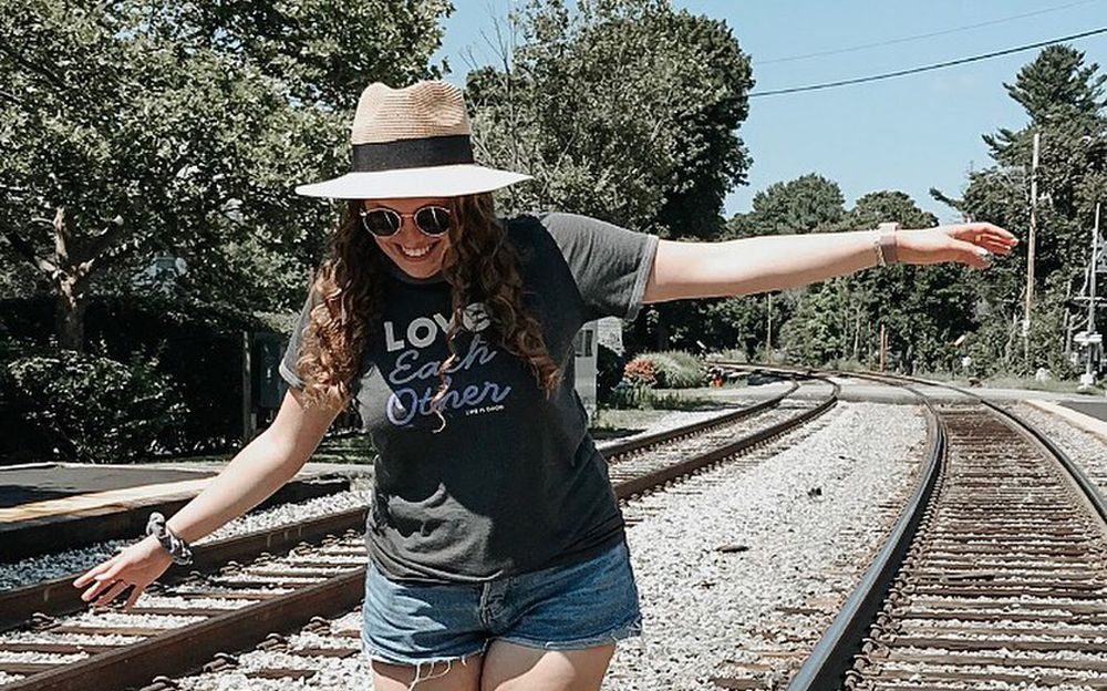 young woman balancing on train tracks smiling
