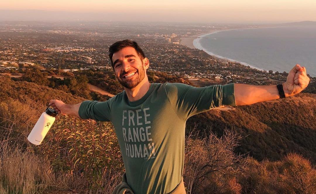 young man celebrating at the top of a mountain