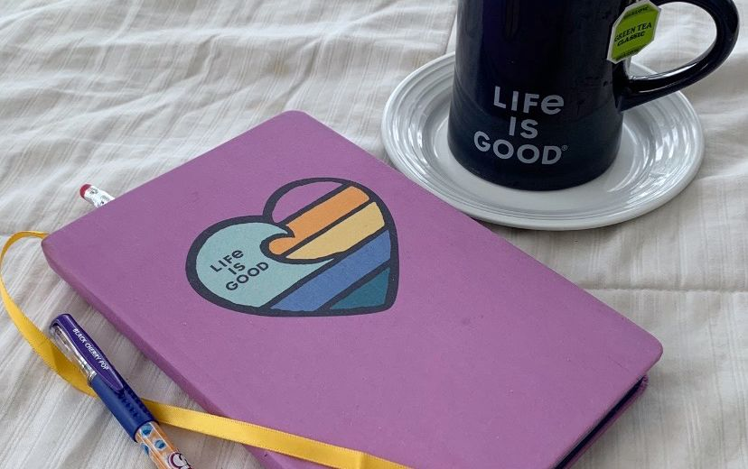 life is good journal, pen and cup of coffee in bed