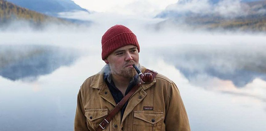 Andy smoking a pipe in front of a foggy lake