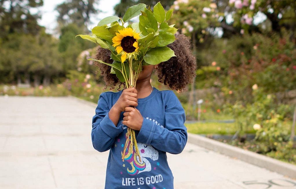 Daughter holding sunflower