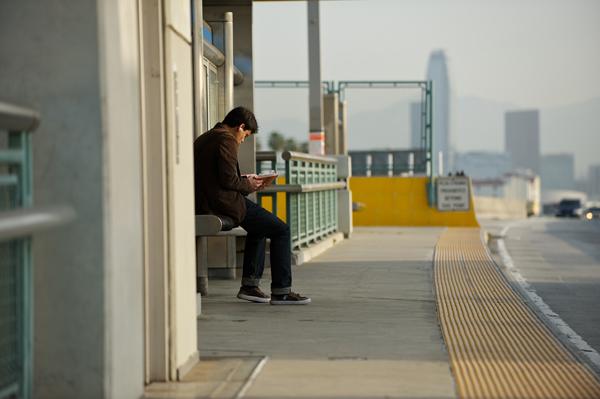 Pasajero en espera del autobús en Harbor Transitway. (Foto Peter Watkins/El Pasajero)