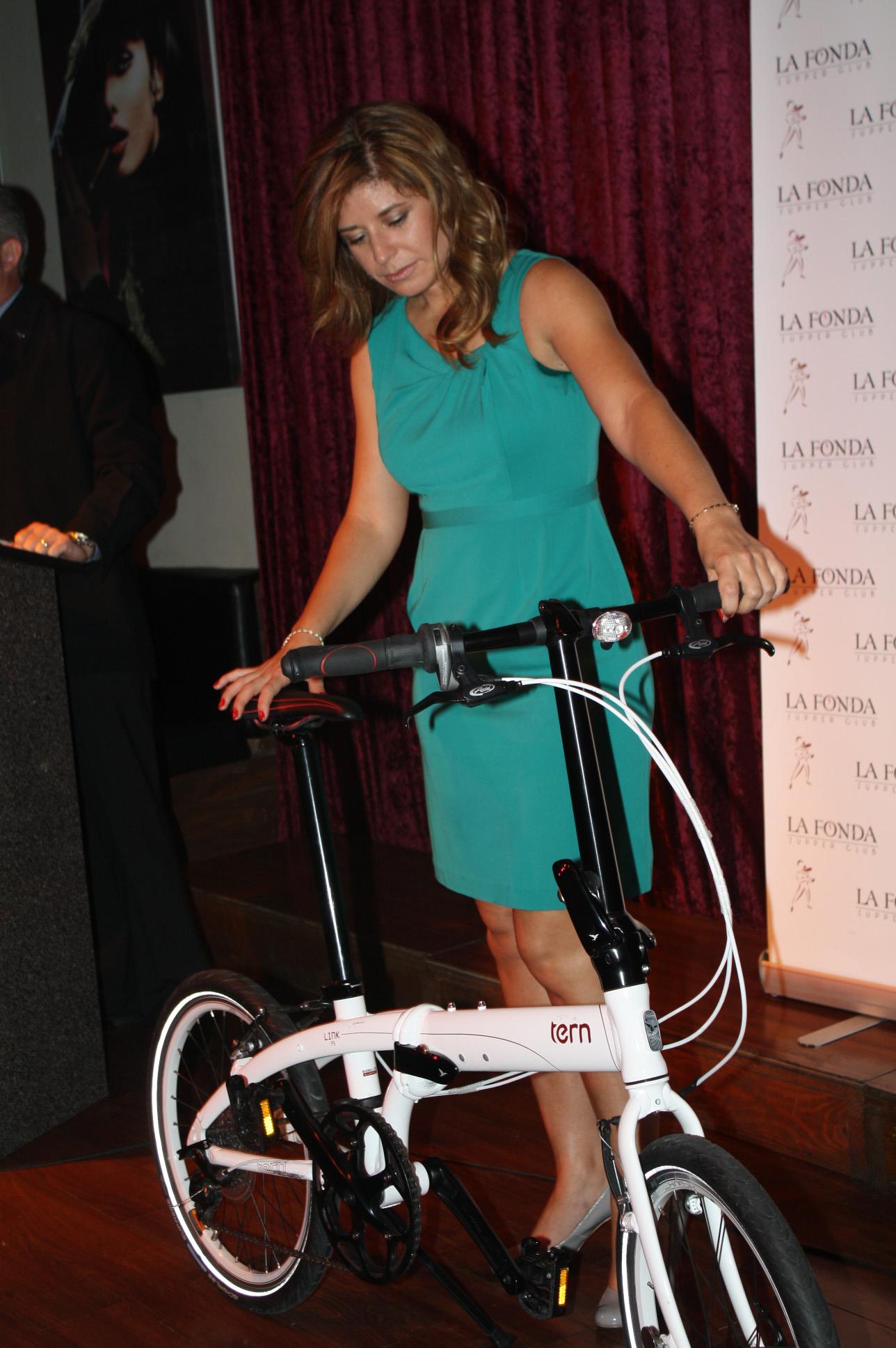 Lourdes López , miembro de la mesa directiva de LACBC, muestra una de las bicicletas subastada. (Foto Agustín Durán/El Pasajero)
