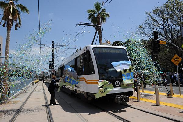 """El tren inaugural rompe el """"listón/bandera"""" que marco la apertura de la Línea Expo."""