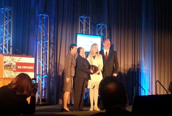 Barbara Burns, directora de Programas de Seguridad de Trenes de Metro y Lynda Bybee, directora interina de Comunicaciones de Metro (segunda y tercera de izq. a der., respectivamente), reciben el premio de APTA.