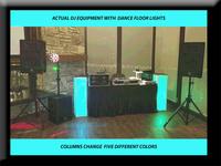 Dj euipment w lit colums and dance floor lights