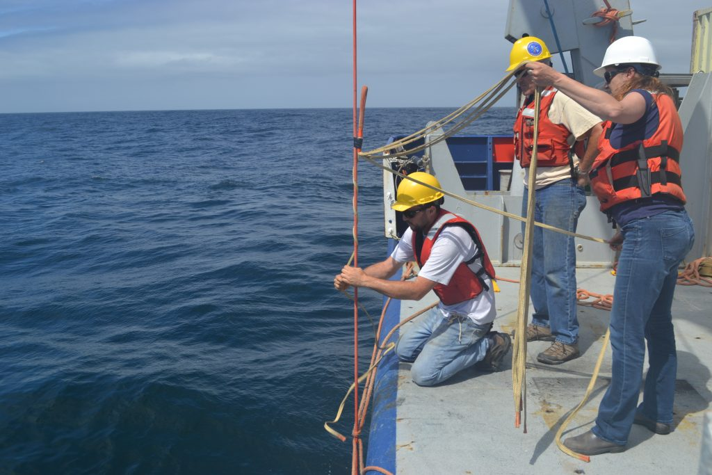 "Nicolas C. Michel-Hart (APL Principal Engineer) attaches a ""Yale"" cable grip to the Offshore Deep Profiler Mooring cable for recovery. Tim M. McGinnis (APL Sr. Principal Engineer) and Trina M. Litchendorf (APL Oceanographer IV) assist. Credit: M. Elend, University of Washington, V18."