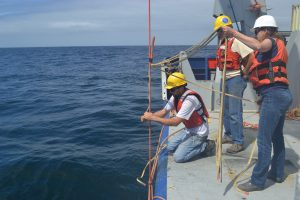 """Nicolas C. Michel-Hart (APL Principal Engineer) attaches a """"Yale"""" cable grip to the Offshore Deep Profiler Mooring cable for recovery. Tim M. McGinnis (APL Sr. Principal Engineer) and Trina M. Litchendorf (APL Oceanographer IV) assist. Credit: M. Elend, University of Washington, V18."""
