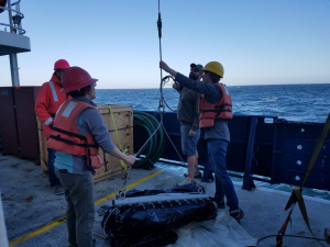 APL post-doc Wu-Jung Lee and Cable Array team member Katie Bigham prep a Tucker trawl net with help from SIO Res Tech Josh Manager. The net was used to collect plankton samples at the Oregon Offshore site. Credit: J. Durant, University of Washington, V18.