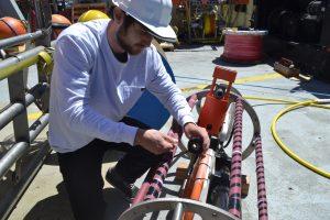 Spencer Nelson secures hosing to the EOM cage on deck. Credit: University of Washington, V18.