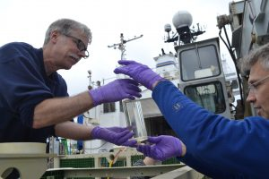 UW Oceanographer Mitch Elend (L) and Co-Chief Scientist Orest Kawka remove samples of hot spring fluids collected 2017-2018 in the remote acces fluid sampler that was capturing fluids from the Tiny Towers diffuse flow site in the International District Hydrothermal Field at the summit of Axial Seamount. Credit: K. Gonzalez, University of Washington, V18.