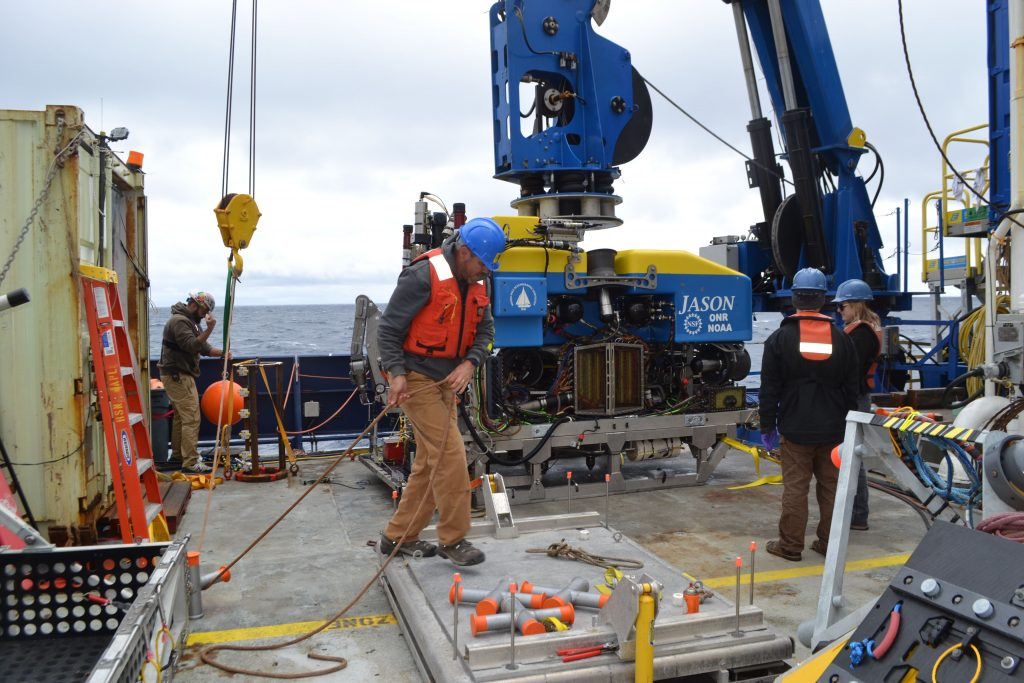 APL engineer James Tilley handles a line to latch a thermistor array under Jason to measure ocean temperatures ~ 1 mile beneath the oceans' surface. Josh Manger, lead Marine Tech onboard the R/V Revelle, directs operations. Credit: M. Elend, University of Washington, V18.