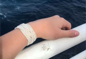 During the off and on pace of the cruise, its good to find calming tasks such as the long-time tradition of making bracelets and knot tying. Credit: A. Larsen, University of Washington, V18.