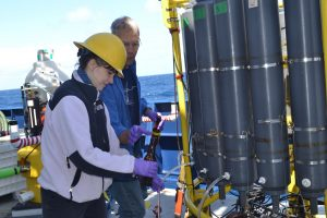 Riah Buchanan, DXARTS Ph.D student at the University of Washington, learns how to process water samples onboard the R/V Revelle from taken >600 ft beneath the oceans'surface. Credit: M. Elend, University of Washington, V18.