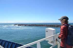 Amy Larsen, UW School of Oceanography undergraduate student, looks out towards the Pacific Ocean as the R/V Revelle transits out of Newport Oregon the first day of Leg 2 of the NSF-OO-UW Cabled Array cruise. Credit: M. Elend, University of Washington. Credit: M. Elend, University of Washington, V18.