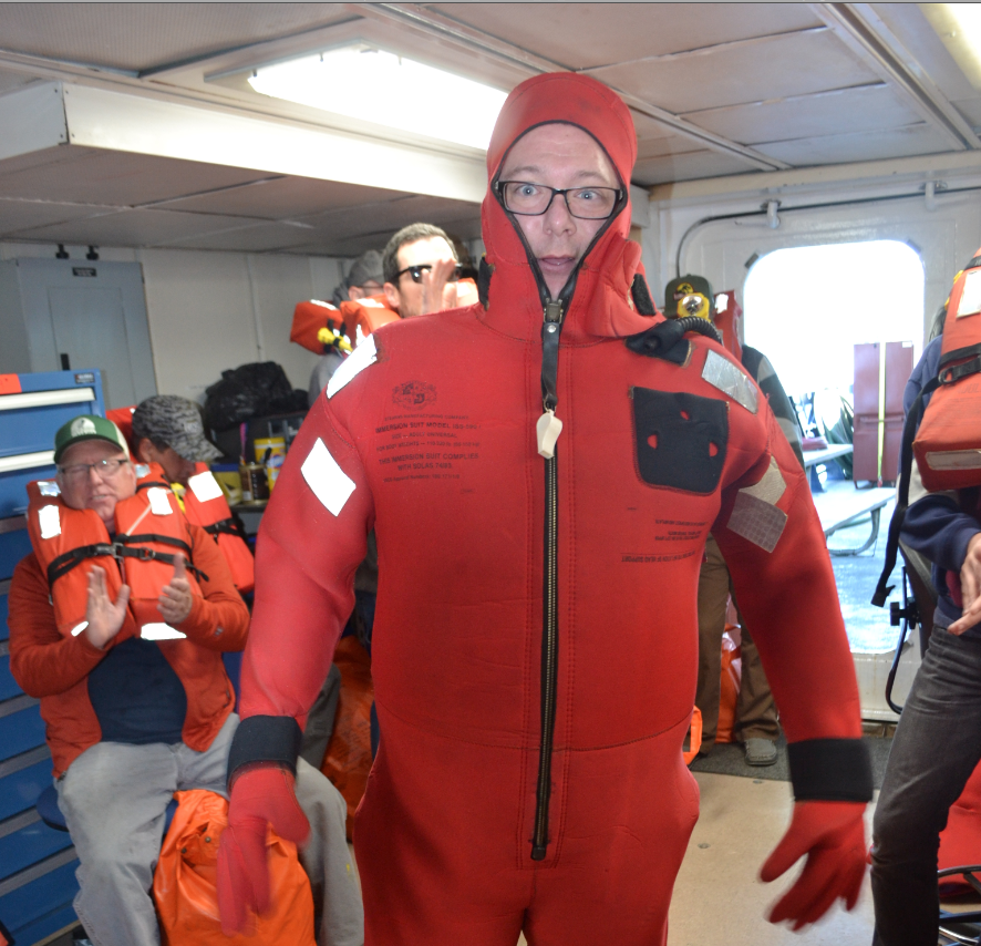 UW School of Oceanography student, Brison Gray, demonstrates getting into a survival suit onboard the R/V Revelle, the first day of Leg 2 of the Cabled Array VISIONS18 expedition. Credit: M. Elend, UW/NSF-OOI/WHOI, V18.