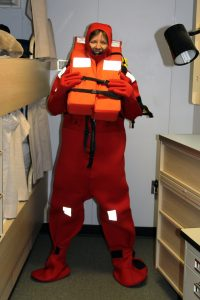 Rachel experiences the fun of trying on a survival (gumby) suit for the first time onboard the R/V Revelle.