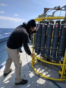 UW Oceanography graduate student Zach Cooper works to set up a CTD to sample deep-sea fluids and the microbes that thrive in the cold, near freezing waters of the NE Pacific. Credit: Sasha Seroy, University of Washington, V17.