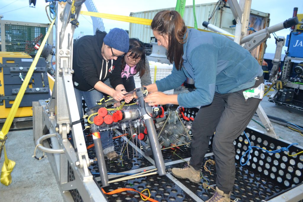 UW students Chanelle Cadot and Michelle Lee help graduate student Theresa Whorley recover the Mosquito benthic flow meters from the Jason elevator used to transport equipment to and from the seafloor. Credit: M. Elend, University of Washington, V17. 	Helping with the Osmotic Fluid Samplers