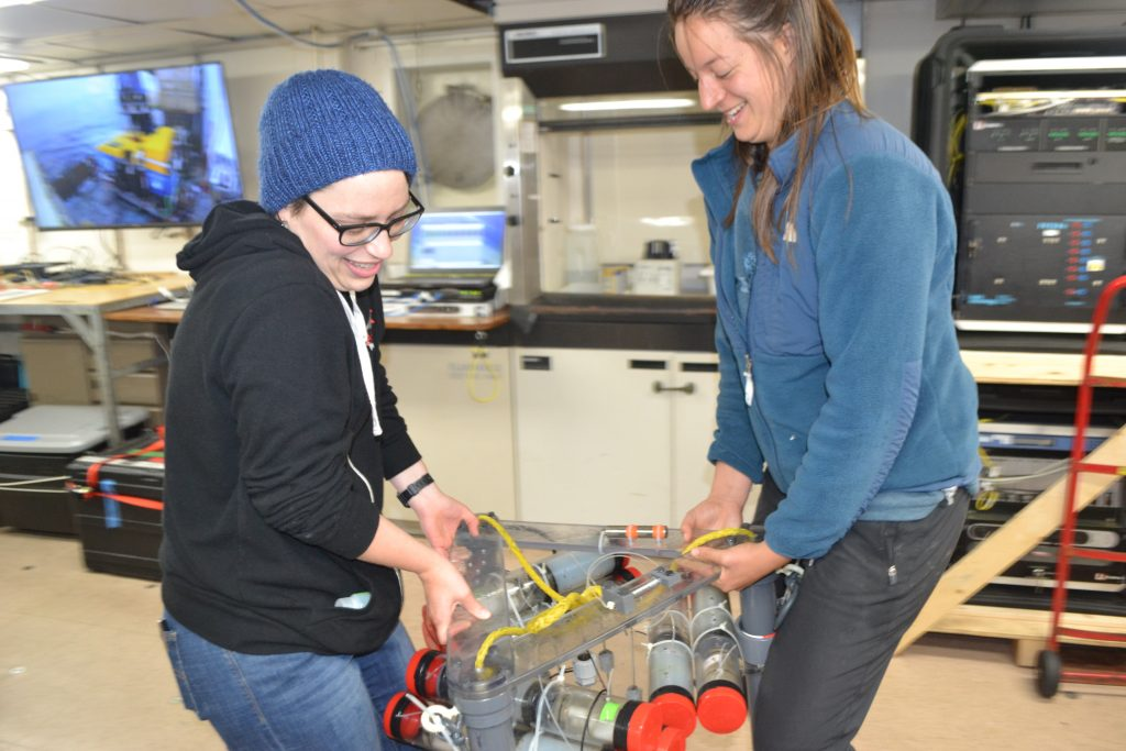 Theresa Whorley (UW School of Oceanography Graduate Student) and Channel Cadot (UW undergraduate) carry an Osmo fluid sampler out to the deck for installation by the ROV Jason during the UW-OOI-NSF Cabled Array expedition. Credit: M. Elend, University of Washington, V17.