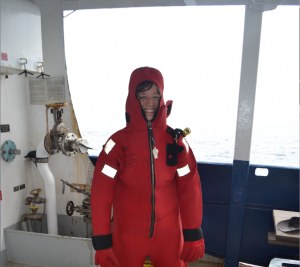 Chanelle tries on a survivial (gumby) suit on the R/V Revelle. Credit: M. Elend, University of Washington, V17.