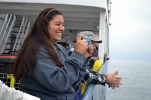 Katie Gonzalez watches a large pod of Pacific White-sided Dolphins ~60-70 km west of Newport, Oregon. Credit: M. Elend, University of Washington, V17.