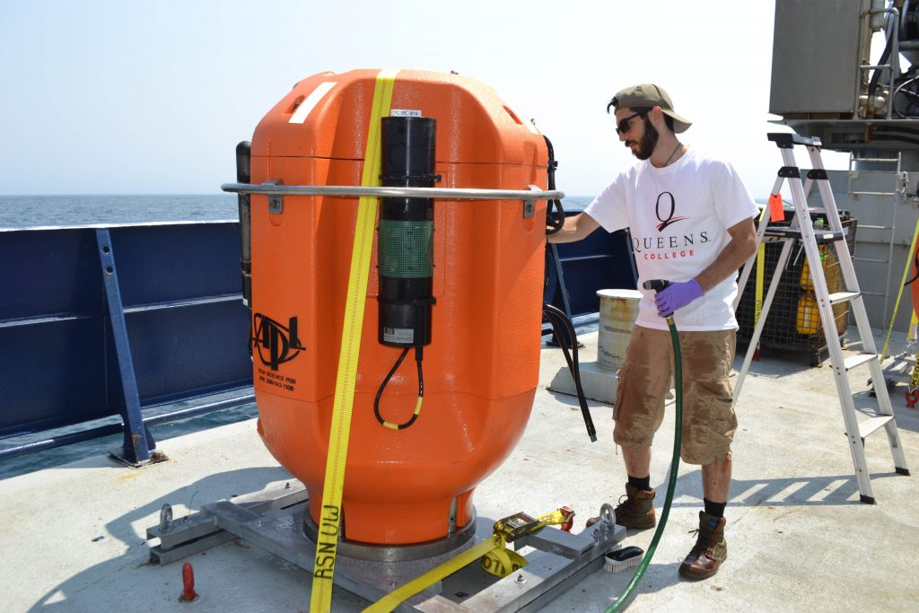 Alex Andronikides from Queens College, New York helps clean a Shallow Profiler Mooring science pod that was installed off the WA-OR coast in 2016. Credit: M. Elend, University of Washington, V17.