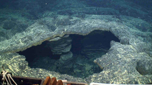 A skylight in the April 2011 lava flows shows where lava had drained out in the subsurface, leaving a cavern. The front porch of the ROV Jason is in the foregound. UW/OOI-NSF/WHOI; J2-980; V17.