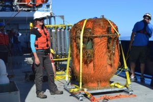 Triana Litchendorf, an engineer with the UW Applied Physics Laboratory observes the Science Pod recovered after a year at 200-50 m beneat the oceans surface. It is covered in biological communities that include smalle scallops and a barnacle. Credit: M. Elend, University of Washington, V17.